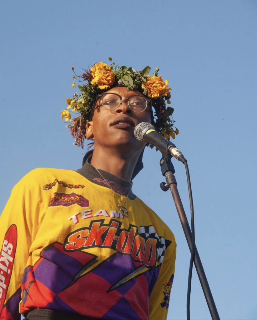 Image of Golden standing behind a microphone with a crown of flowers